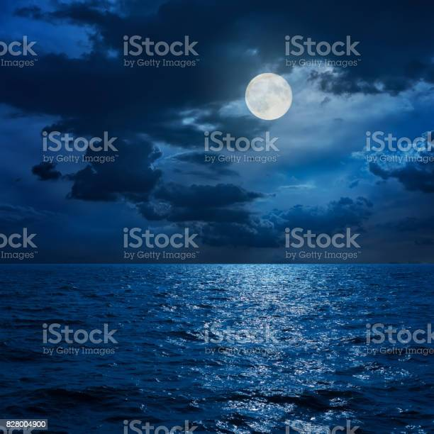 Photo of full moon in clouds over sea in night