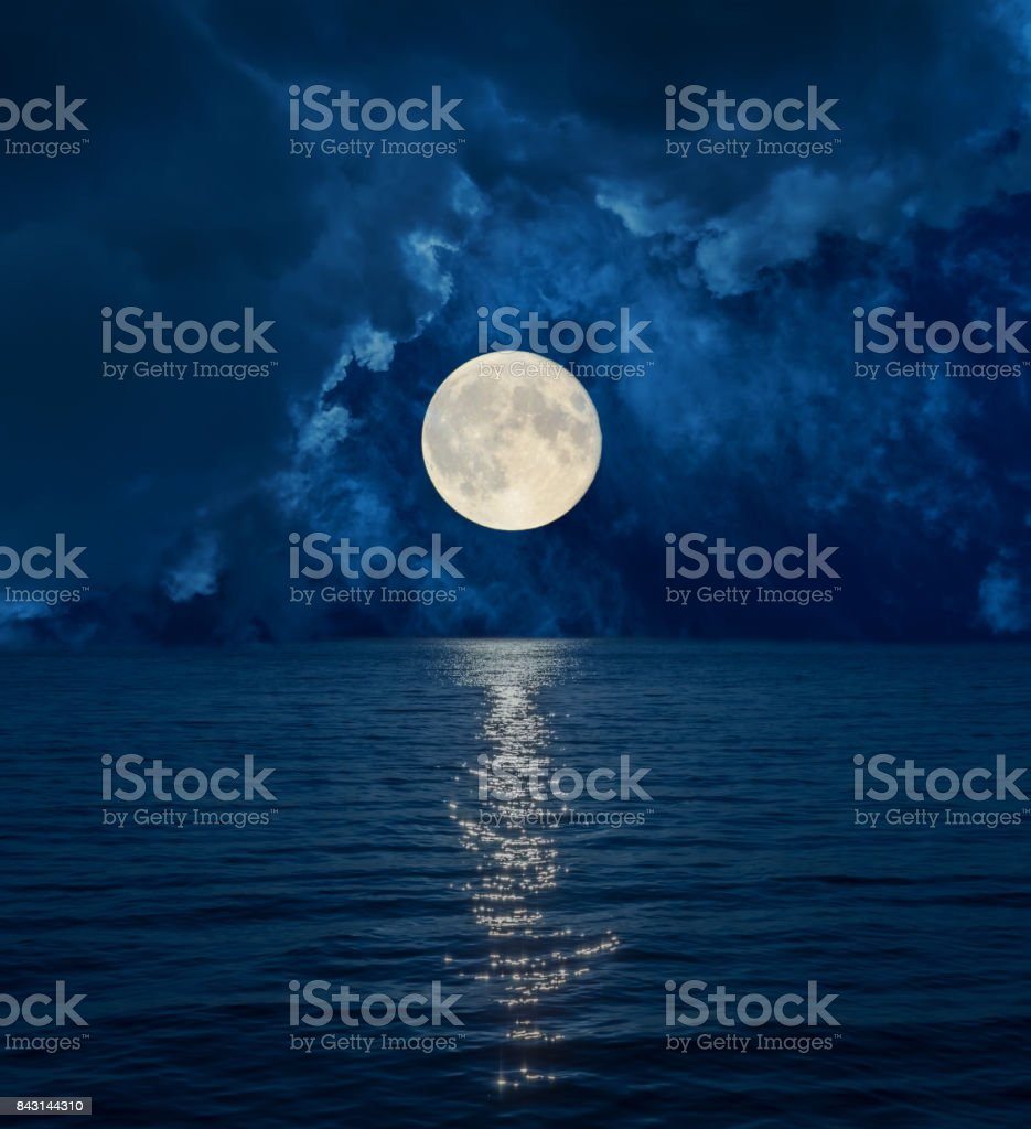 full moon in dark clouds over sea stock photo