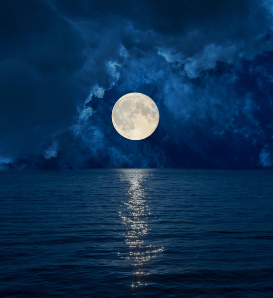 full moon in dark clouds over sea - romantic moon stock photos and pictures