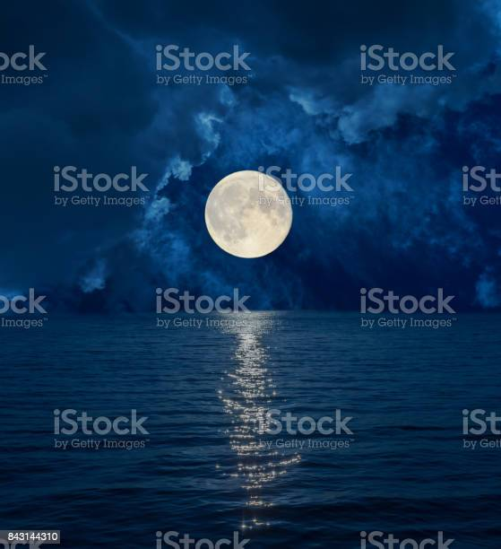 Photo of full moon in dark clouds over sea