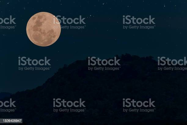Photo of Full moon on the sky with mountain silhouette at night.