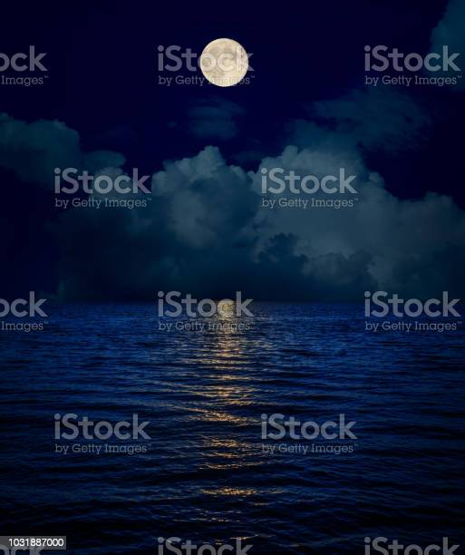 Photo of full moon over clouds and dark water with reflections