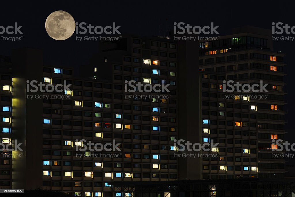 Full moon over colorful windows of residential house stock photo