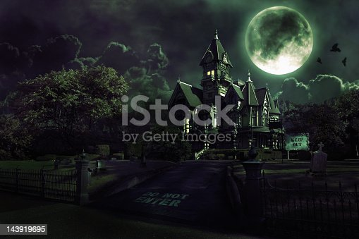 Dark image of a haunted house with clouds and mountains in the background. Includes graveyard, full moon, and crows flying across moon. Copy space. CLICK FOR SIMILAR IMAGES AND LIGHTBOX WITH SEASONAL IMAGES.