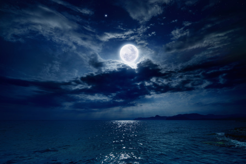 Night sky with full moon and reflection in sea, stars, beautiful clouds. Elements of this image furnished by NASA