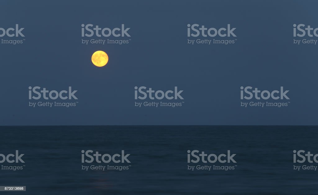 full moon over the ocean by night stock photo