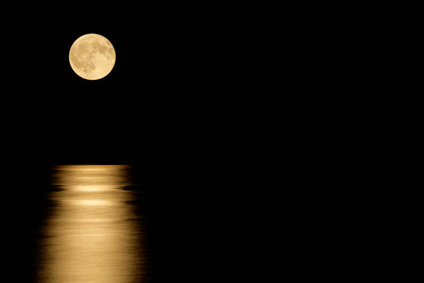 full moon over the sea at night (with copyspace) - romantic moon stock photos and pictures