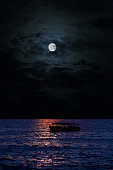 full moon over the sea, dark clouds, the silhouette of the ship against the water