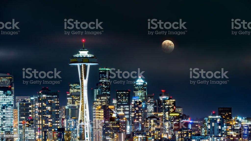 Volle maan stijgt boven de skyline van Seattle foto