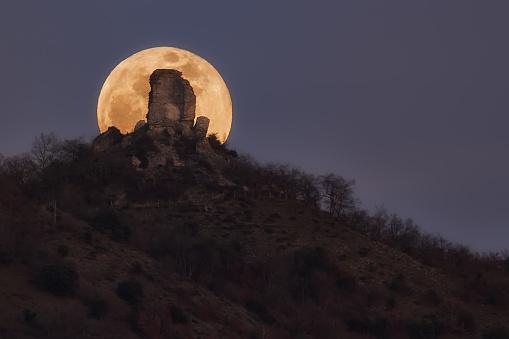 Full moon rising behind Gebara castle ruin in Alava