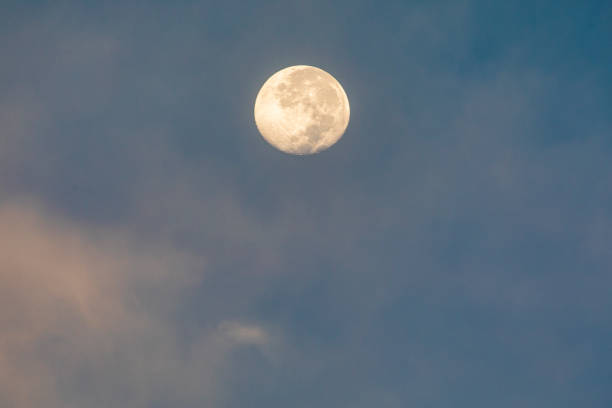 Full moon rising in light pink sky and blue background stock photo