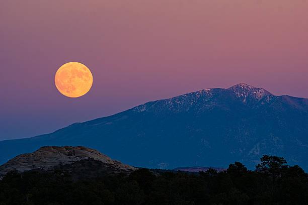 Full Moon Rising Over Desert and Mountains stock photo
