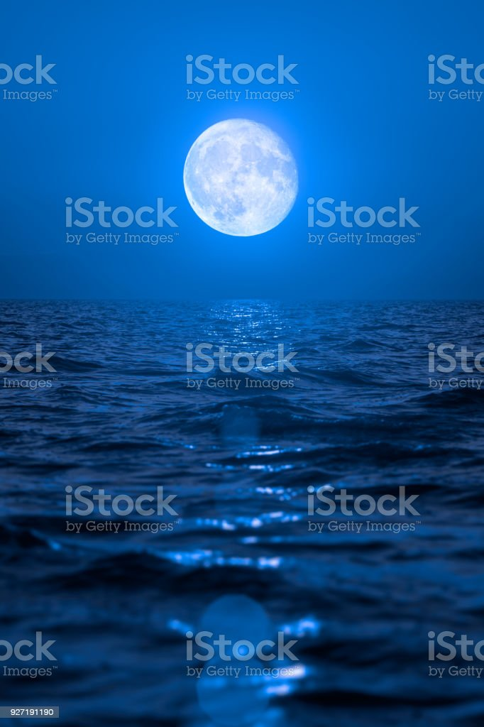 Full moon rising over empty ocean at night stock photo