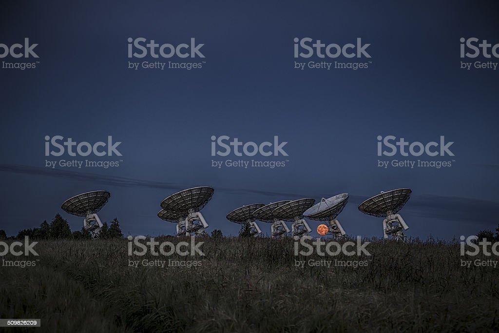 Full moon rising over satellite dish stock photo