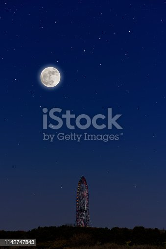 Full moon rising over the Ferris Wheel and lots of stars with copy space.
