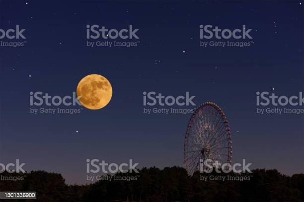 Photo of Full moon rising over the Ferris Wheel