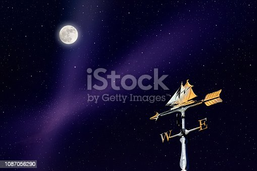 Full moon and lots of stars rising over the sailboat weather vane.