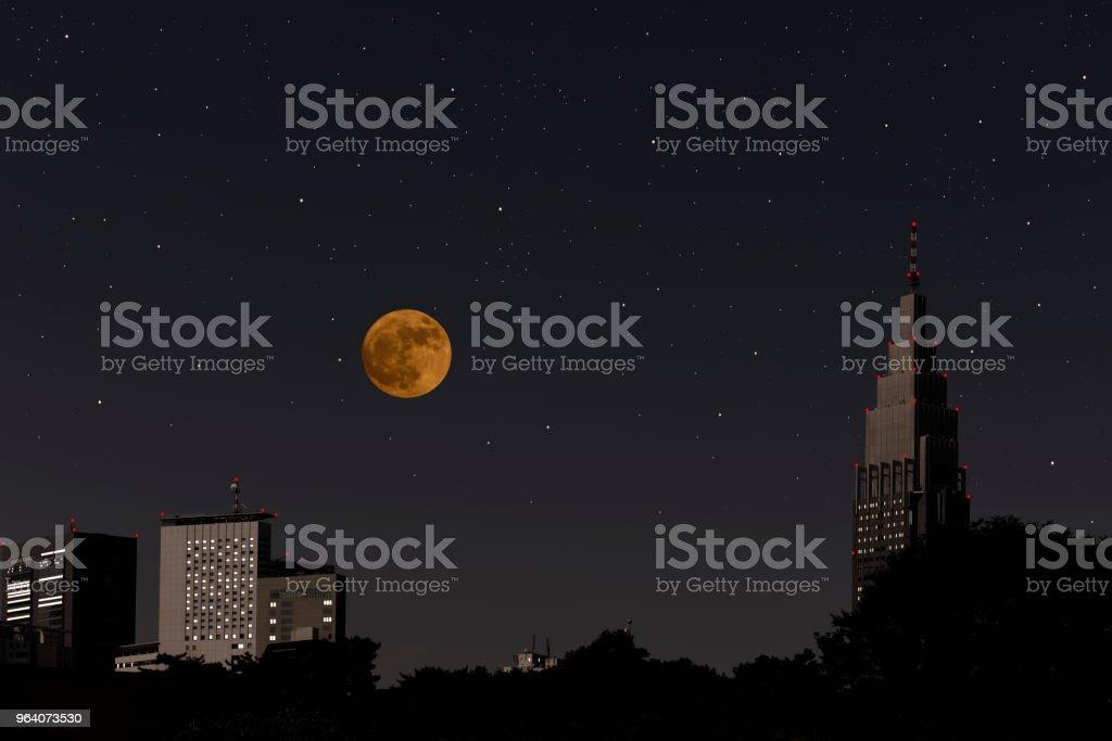 高層ビルや多くの星をかけて上昇満月 - イルミネーションのロイヤリティフリーストックフォト