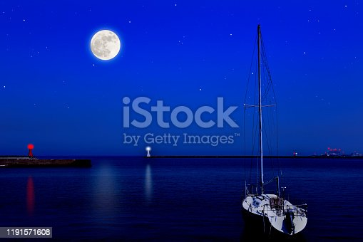 1039894076 istock photo Full moon rising over the Yacht and the lighthouse. 1191571608