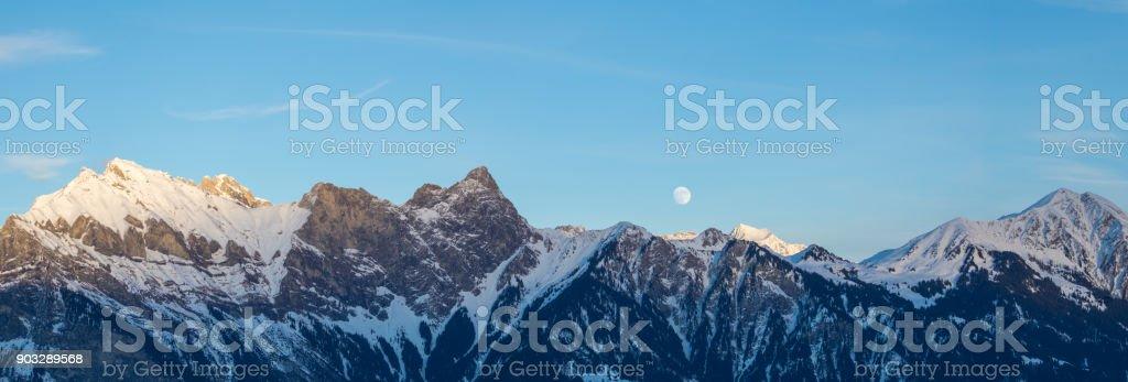 full moon rising over winter mountain landscape stock photo