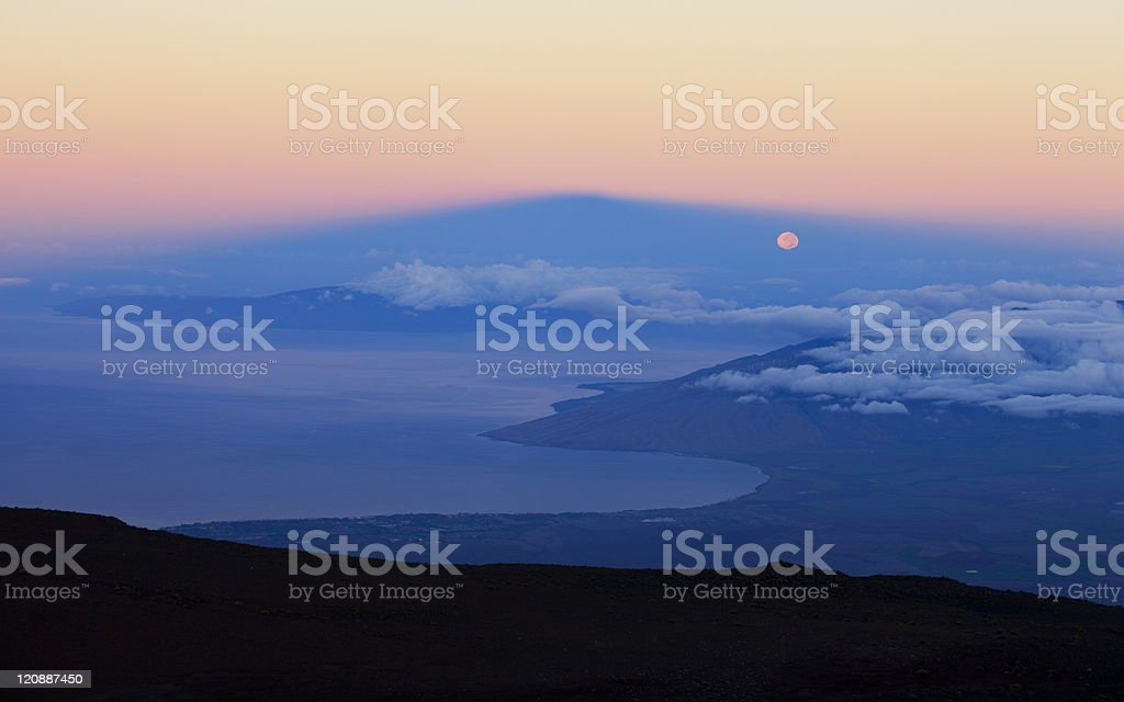 Full moon setting in Volcano's shadow royalty-free stock photo
