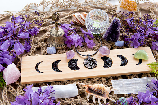 Full Moon Witch Pagan Moon Phases Altar with crystals of selenite and amethyst, with candle, pentacle and purple flowers