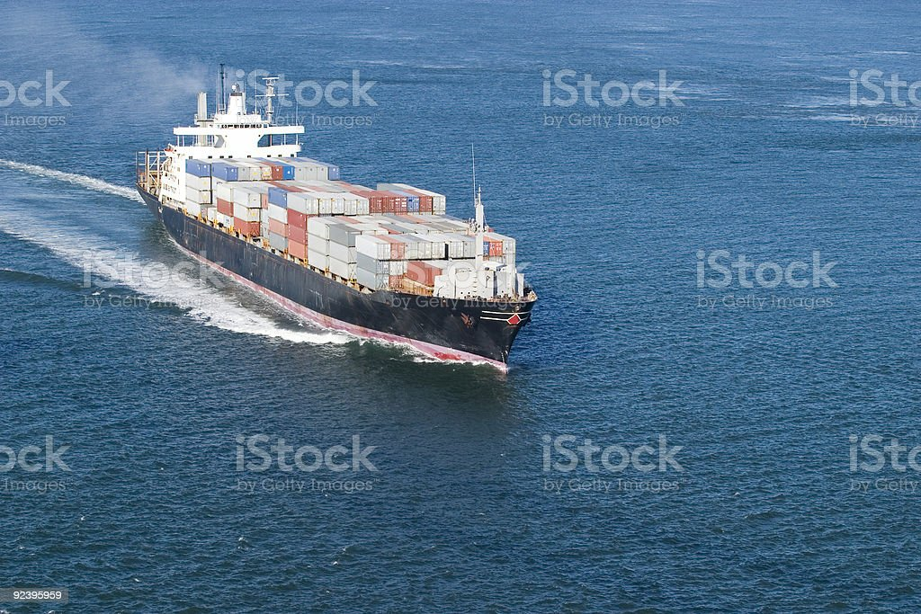 A full moving container ship with steam on blue water royalty-free stock photo