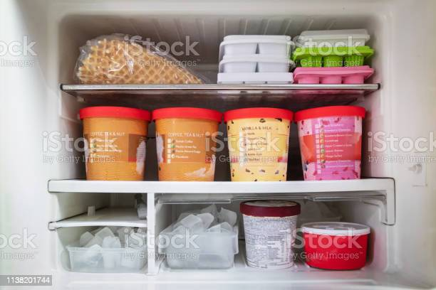 Photo of Full of bucket container ice creams flavors and ice cubes in freezer.