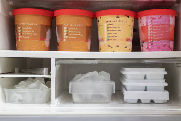 full of bucket container ice creams flavors and ice cubes in freezer. - gelato confezionato foto e immagini stock