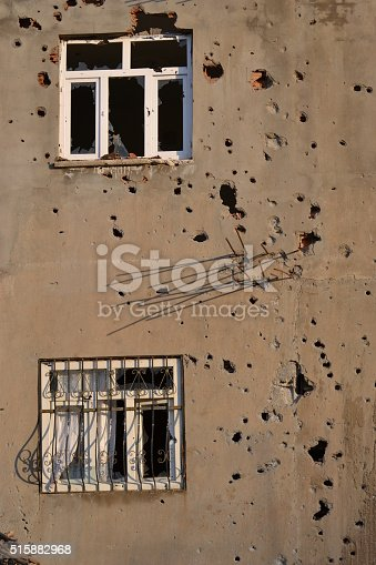691128564istockphoto full of bullet holles and broken windows 515882968