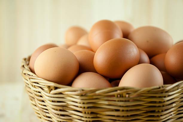 full of eggs put in a wicker basket - fresh start yellow stockfoto's en -beelden