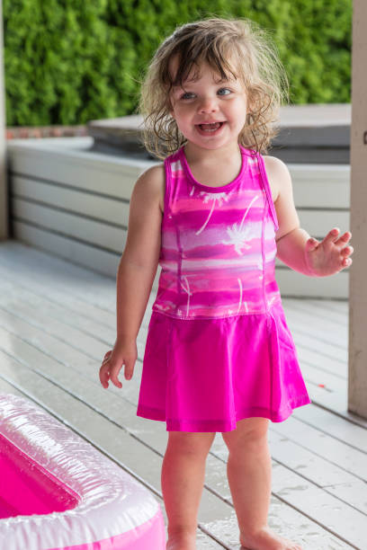 Full of joy describes this pretty, grinning, toddler girl, dressed appropriately in brilliant pink. A beautiful little girl, with the messy hair of a carefree spirit, captures your heart with her smile and demeanor. appropriately stock pictures, royalty-free photos & images