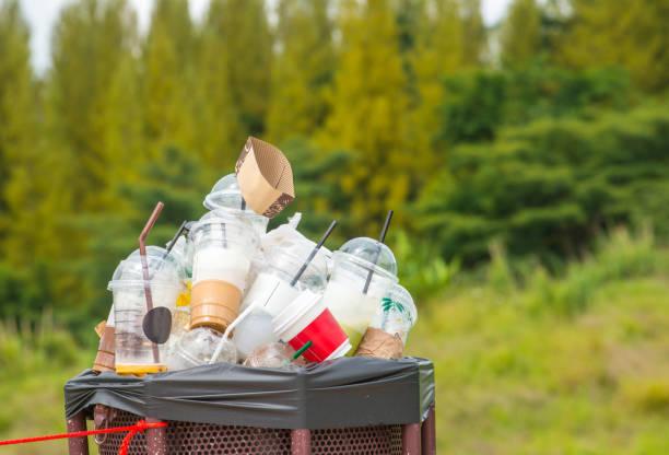 Voller Plastikbecher im Papierkorb in der Natur. – Foto