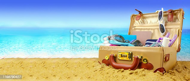 istock Full open suitcase on tropical beach background, banner 1168790427