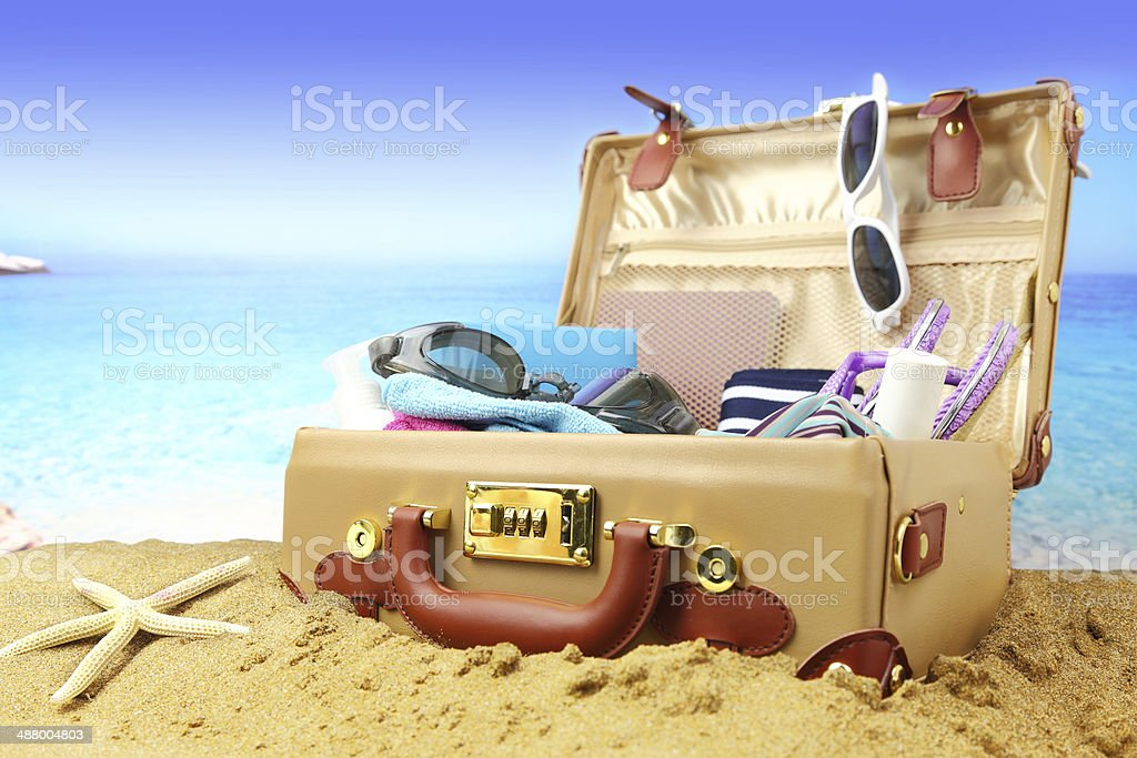 Full open suitcase on tropical beach background stock photo