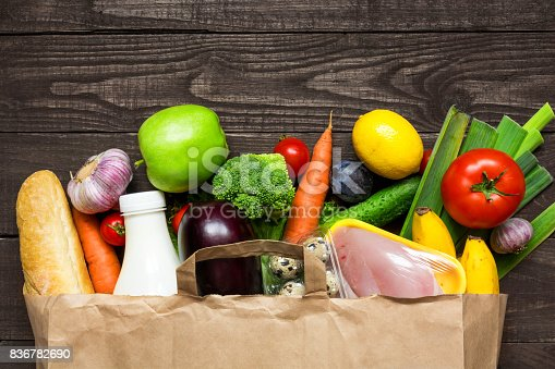 istock Full paper bag of different health food on rustic wooden background 836782690