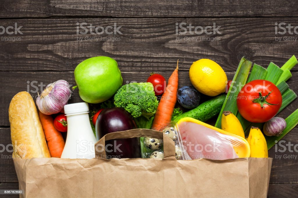 Full paper bag of different health food on rustic wooden background stock photo