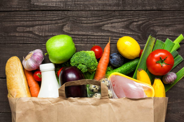 full paper bag of different health food on rustic wooden background - verdura cibo foto e immagini stock