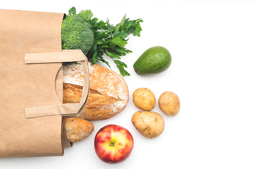 Full paper bag of different health food on white