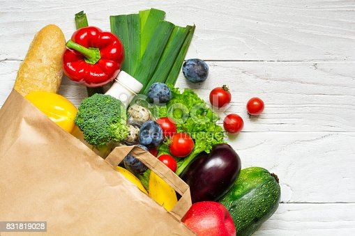 1126188273 istock photo Full paper bag of different health food on white wooden background 831819028