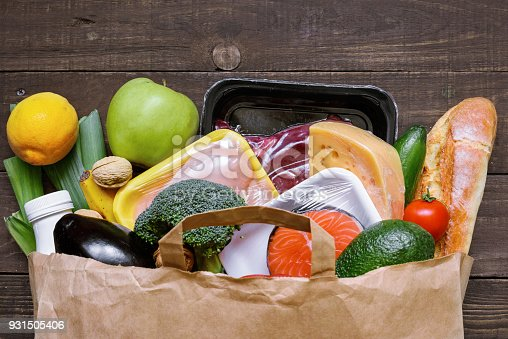 1126188273 istock photo Full paper bag of different healthy food on white wooden background. fruits, vegetables, fish and meat 931505406