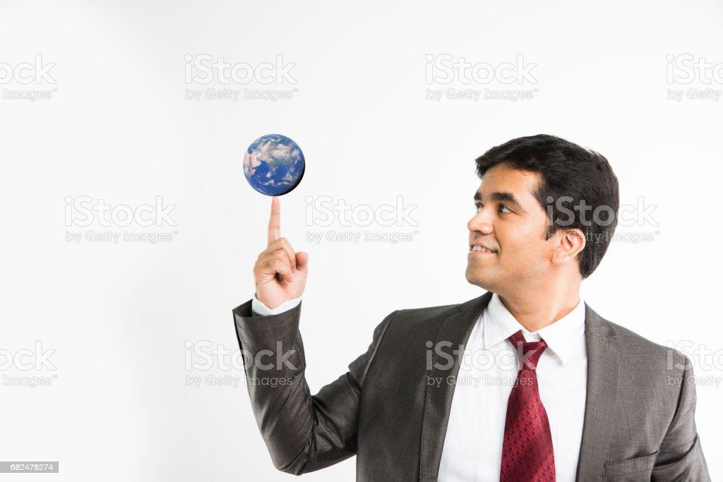 volle Bild des indischen jungen Geschäftsmann Blick in die Kamera beim balancing blauen Globus oder Earth-Modell auf Zeigefinger und tragen komplette corporate Kleidung wie Anzug und Krawatte, isoliert auf weißem Hintergrund Lizenzfreies stock-foto