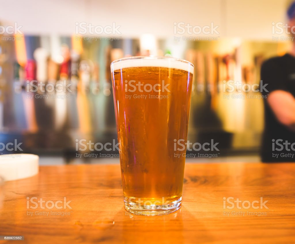 Full pint of beer on the bar stock photo