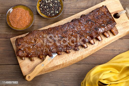 a full rack of ribs on cutting board with spice and peppers