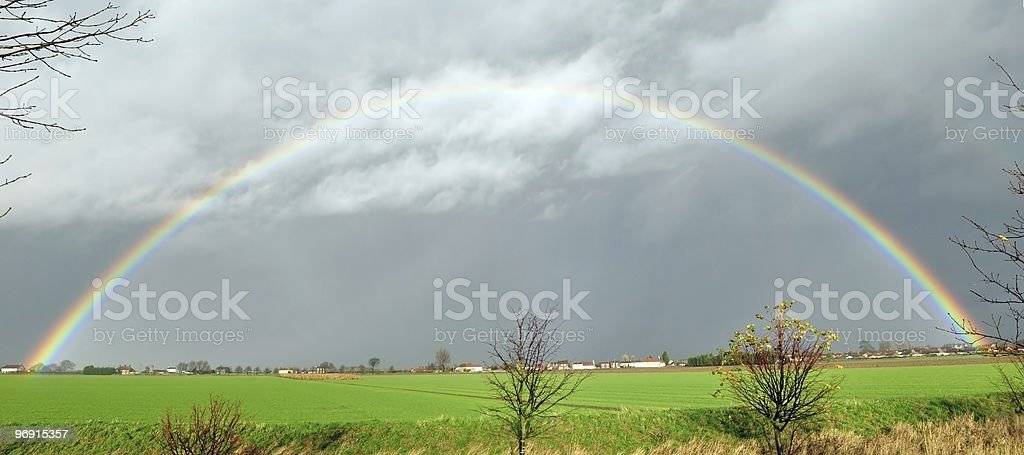 Full Rainbow arch over field and houses royalty-free stock photo
