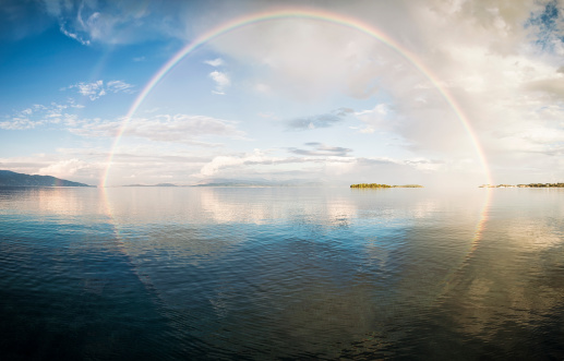 Panorama of a full rainbow reflected in calm water.