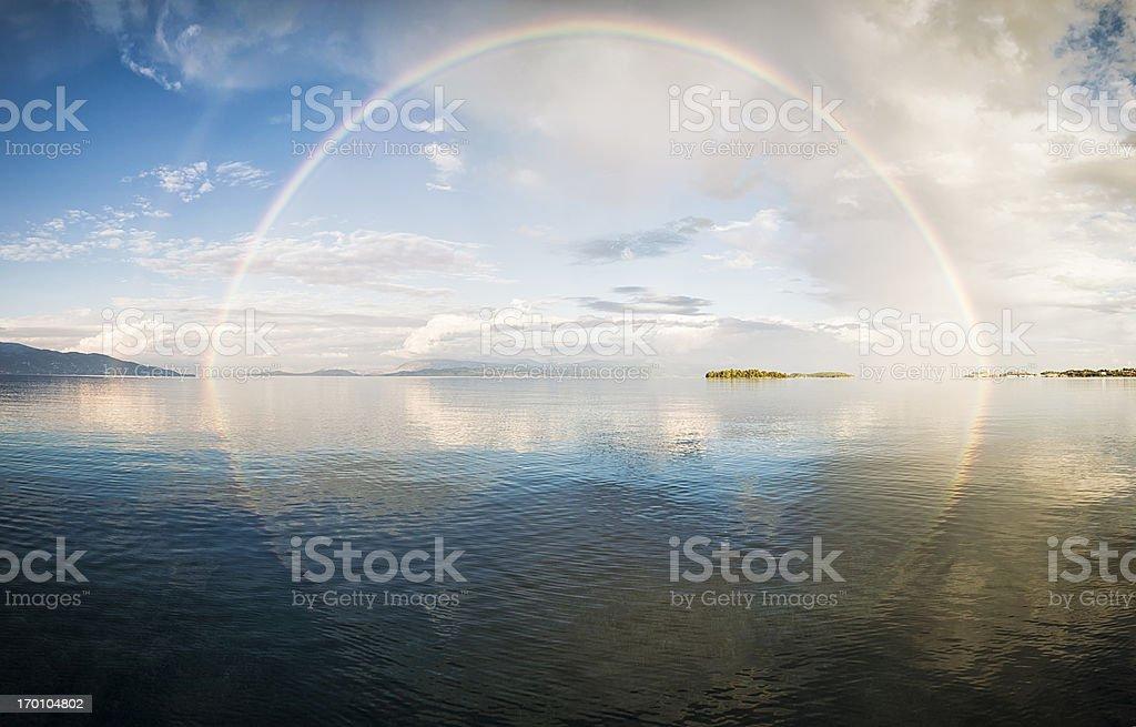 Full rainbow over the sea stock photo