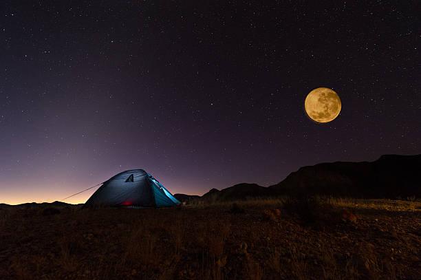 Durchgehender Roter Mond und Sternen über beleuchtete Zelt in der Wüste – Foto