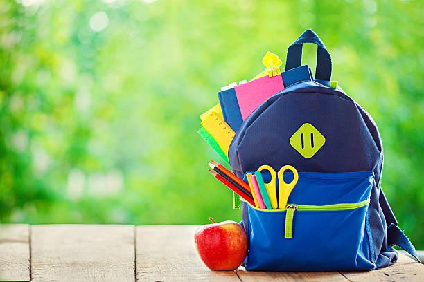 Un sac à dos école avec pomme sur fond en bois et de nature. - Photo