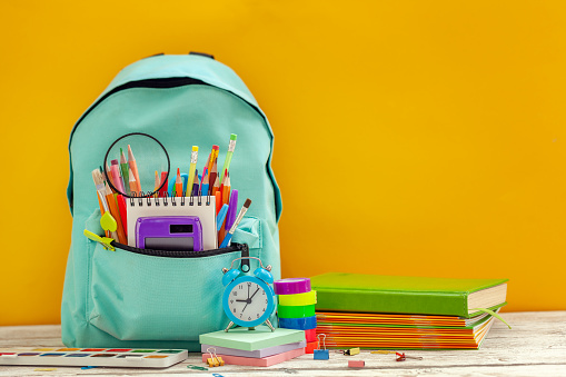 istock Full School Backpack with different supplies on orange background. Concept back to school. 1164521179